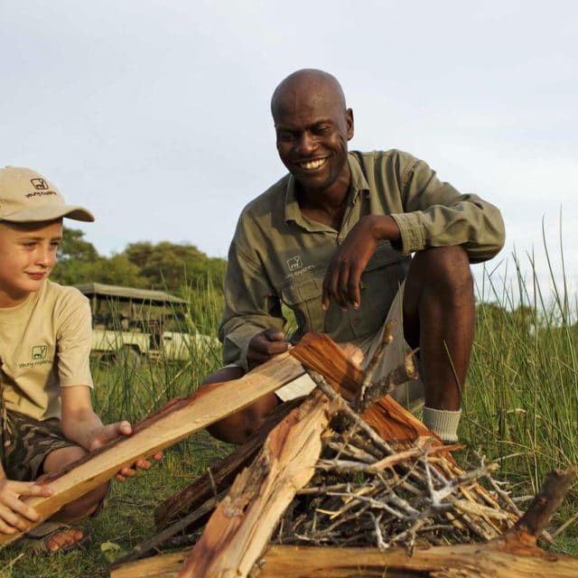 kid learning to build a fire at footsteps